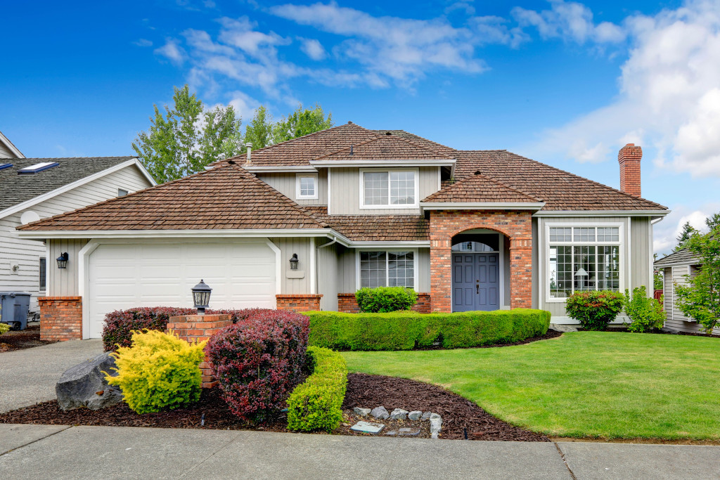 Classic house exterior with brick trimmed entrance porch green lawn and trimmed hedges. Garage with driveway